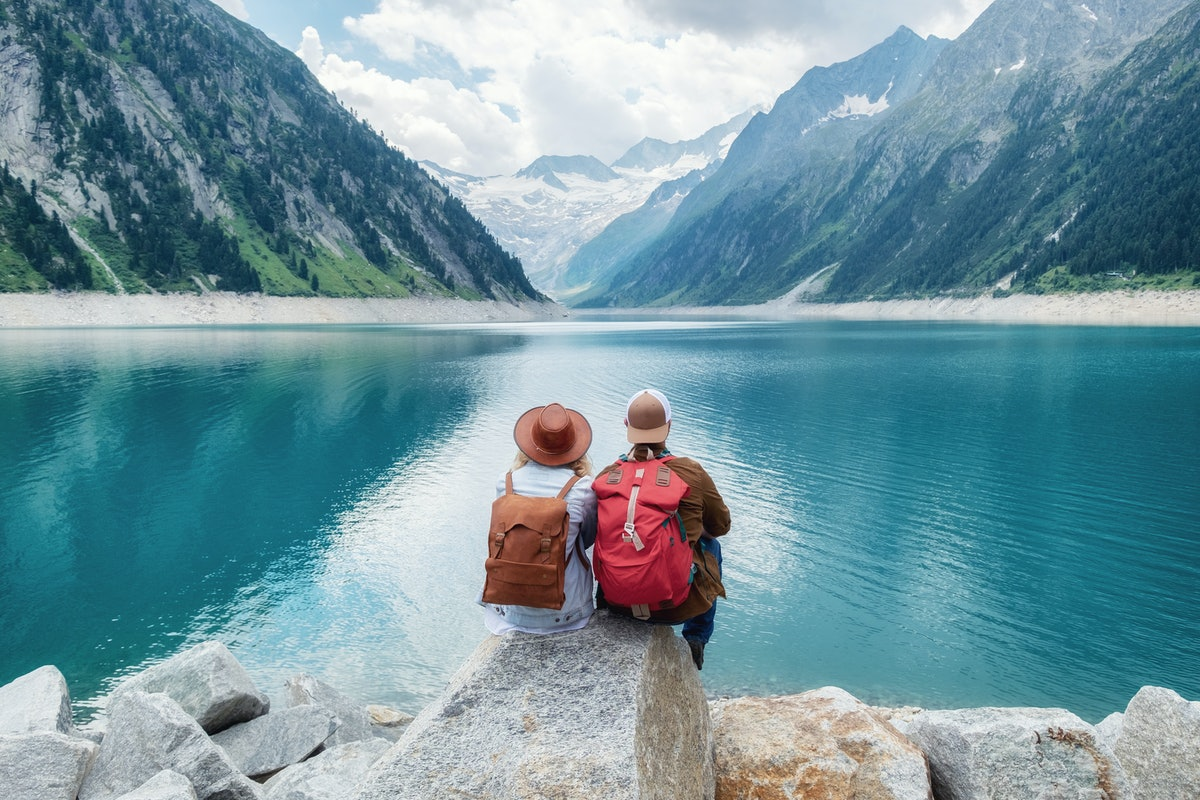 Travelers couple look at the mountain lake. Travel and active life concept with team. Adventure and ...