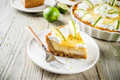 Homemade sweet cake, classic key lime pie with fresh limes, on wooden background copy space