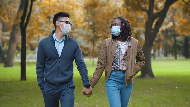 Multiethnic couple in protective masks holding hands walking in park. Lovely diverse man and woman on romantic date strolling in autumn park wearing safety mask