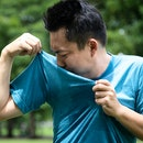 Asian young man feel bad,smelling something stinks,sniffing his wet armpit or sweating a lot because of hot weather or after exercise in outdoor park,male facial expression,concept of using deodorant