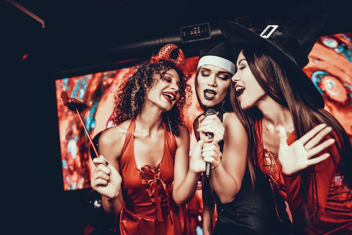 Young Women in Halloween Costumes Singing Karaoke. Happy Smiling Friends Wearing Costumes having Fun...