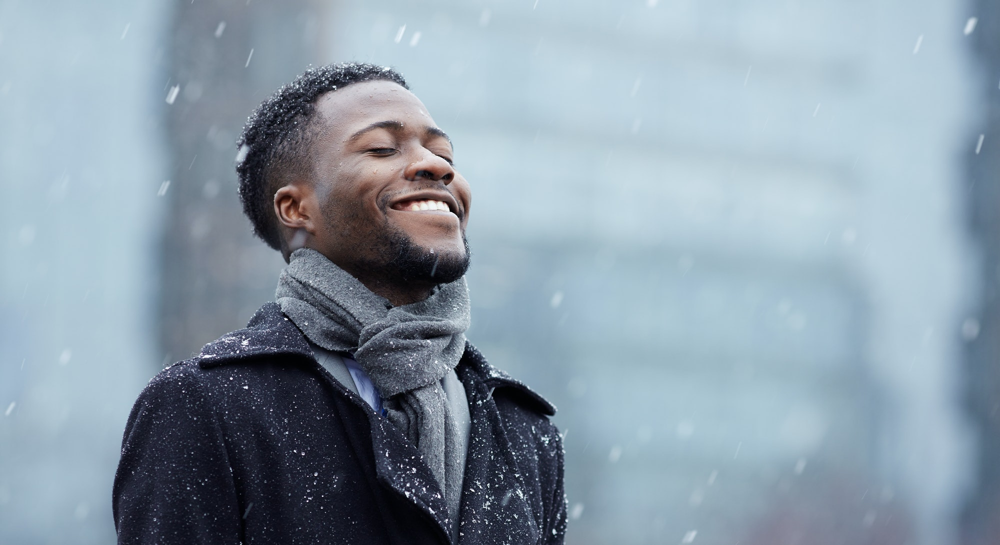 Cheerful man enjoying snowflakes falling from upwards