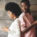 Young African couple standing back-to-back, holding mobile phones. Jealous possessive black man looking over his shoulder at his girlfriend trying to see what she is texting and who she is messaging