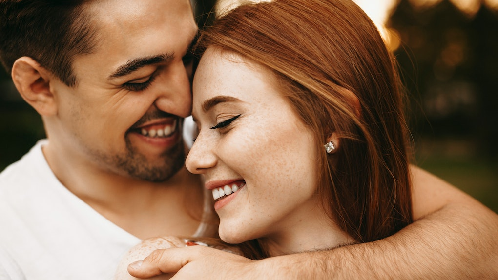 Close up portrait of a amazing young female with red hair and freckles smiling with closed eyes while being embraced from back by her boyfriend closely outside.