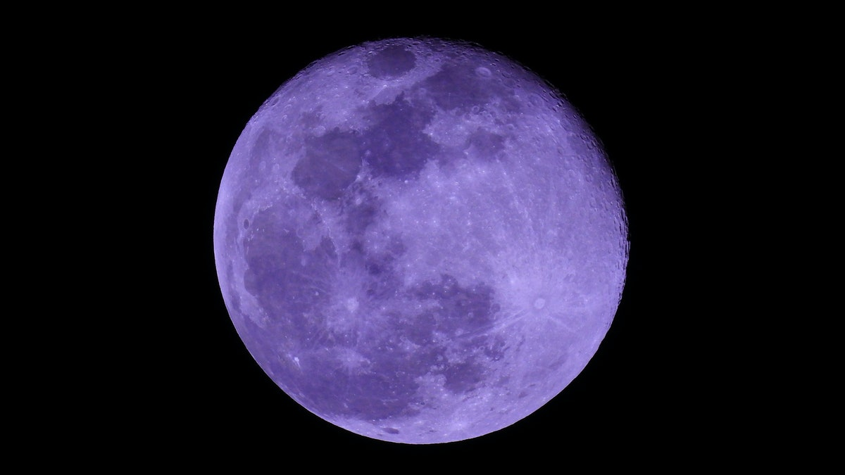 Extreme zoom photo of purple full moon as seen in deep darkness