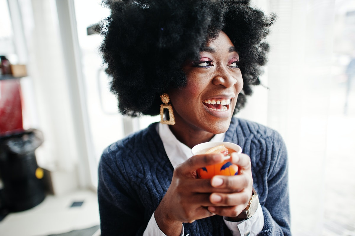 Curly hair african american woman wear on sweater posed at cafe indoor with cup of tea or coffee.
