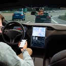 A man reads news online in a smartphone while his car is driven by an autopilot. Self driving vehicle concept