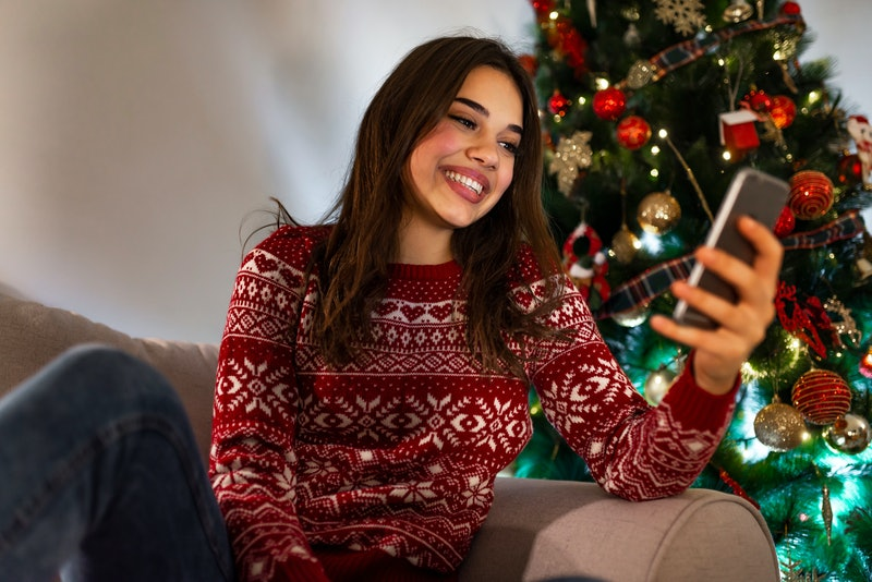 Woman texting on smartphone with christmas tree. Happy woman reading text on a phone on christmas lying on a couch in the living room at home. Call friends and family for christmas wishes.