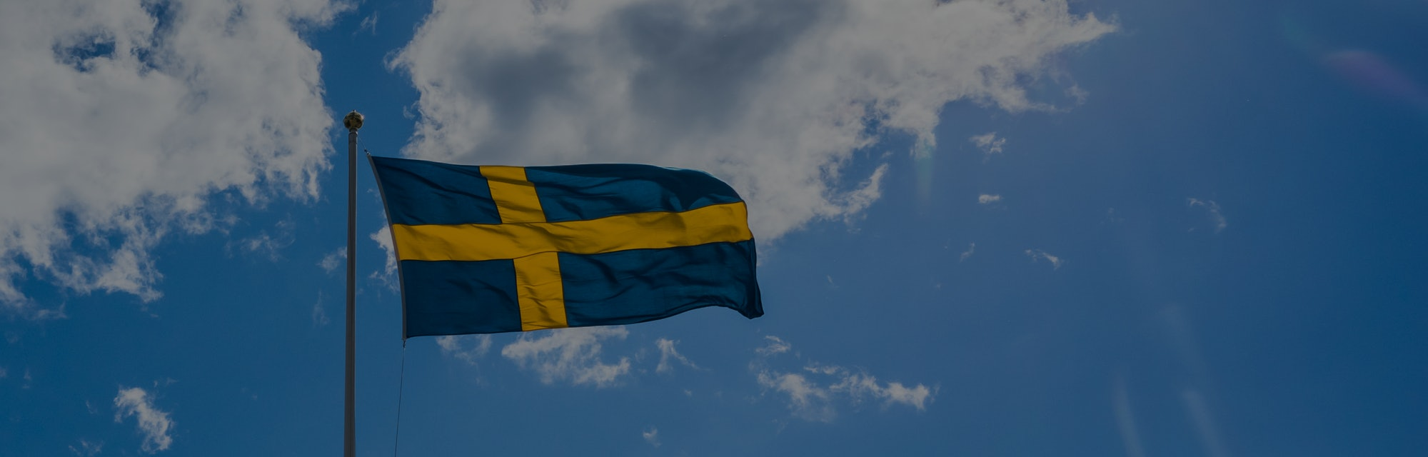 Swedish Flag on blue sky white clouds. Swedish Flag Day concept in Sun rays . Sveriges nationaldag. National Day of Sweden.