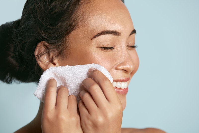 Woman cleaning facial skin with towel after washing face portrait. Beautiful happy smiling young asian female model wiping facial skin with soft towel, removing makeup. High quality studio shot