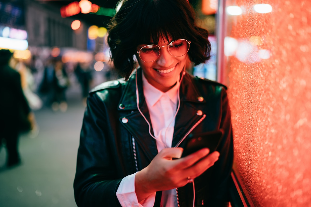 Happy hipster girl in optical spectacles checking shared video web content listening sounds in electronic headphones, trendy dressed blogger communicating with followers from website using smartphone