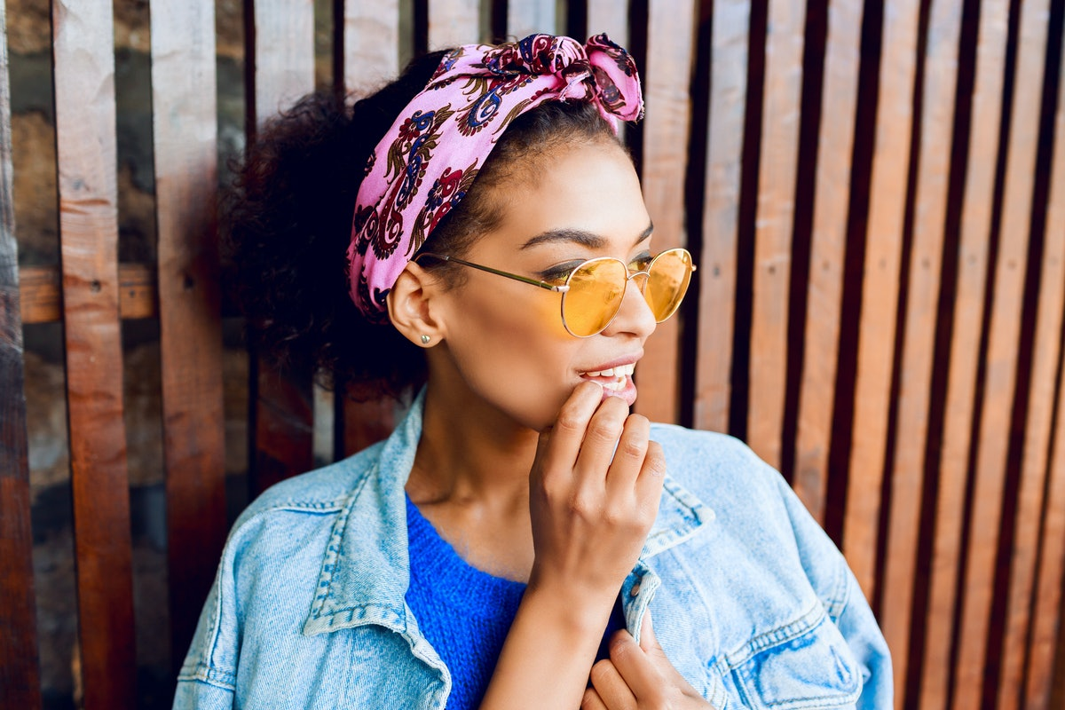 Close up lifestyle  portrait of stylish pretty mixed woman with brown skin and Afro hairstyle with headband  posing near wood wall . Urban look. Fashionable clothes.