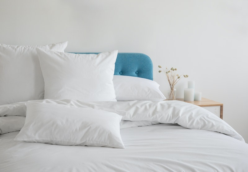 White pillows, duvet and duvet case on a blue bed. White bed linen on a blue sofa. Bedroom with bed and bedding. Messy bed. Front view.