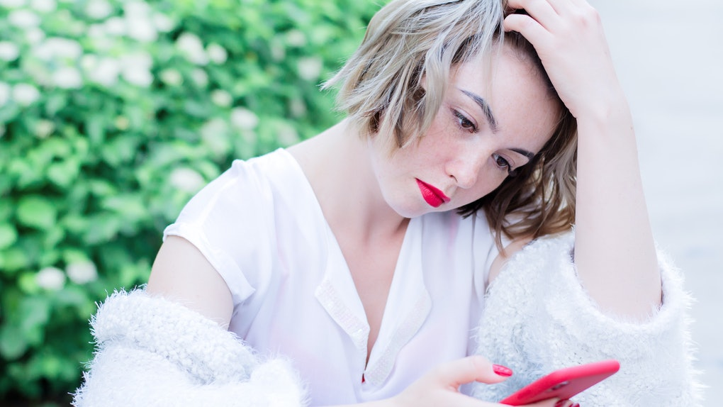 Attractive girl with red lips and manicure is sitting in the park drinking coffee and holding red phone in her hands