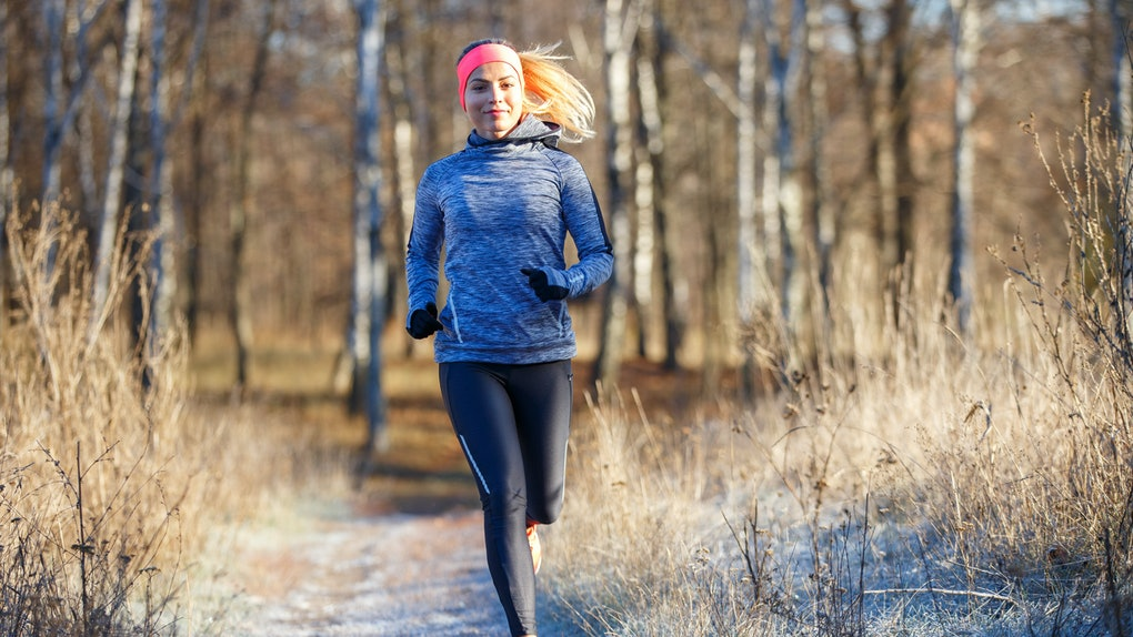 Young slim girl running in the park in early winter. Attractive woman jogging on snowy trail