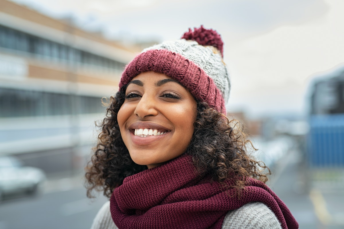 Closeup face of young happy woman enjoy winter, wearing scarf and woolen cap. Smiling black girl looking away outdoor. Carefree african american woman with knitted hat and woolen scarf outdoor.