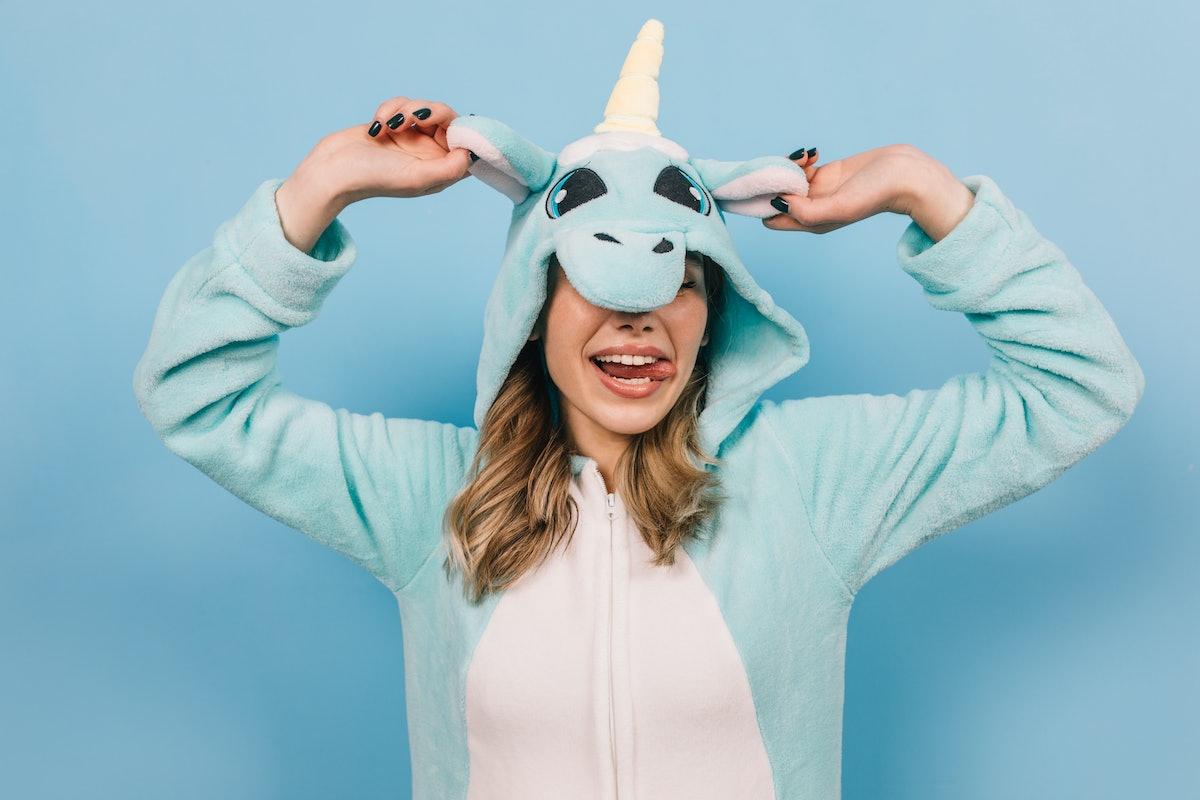 Positive young woman posing in funny pajama. Indoor shot of blissful girl in unicorn kigurumi.