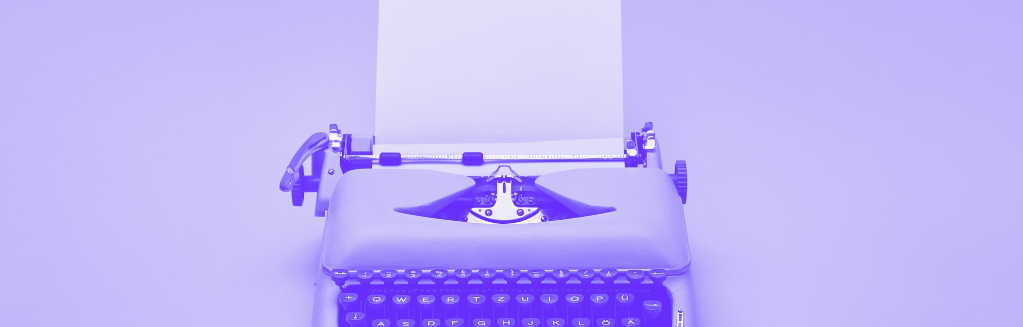 Chic retro typewriter with a paper sheet on the yellow background in the studio.