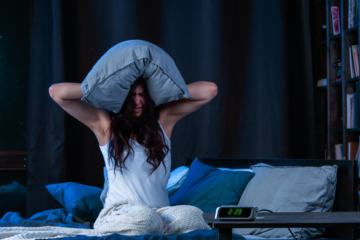 Image of brunette with insomnia with pillow on head sitting on bed