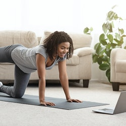 A person smiles at her laptop while doing Pilates at home. Modifying Pilates moves to suit your body's needs isn't cheating, it's making your workout as effective as can be.