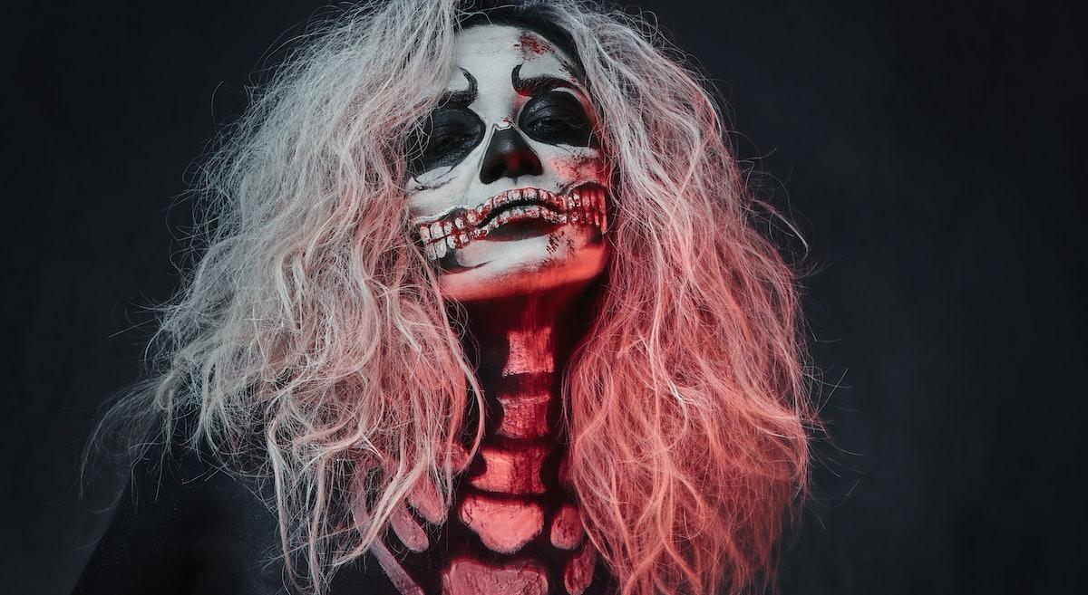 Halloween female skull makeup over dark grey background.