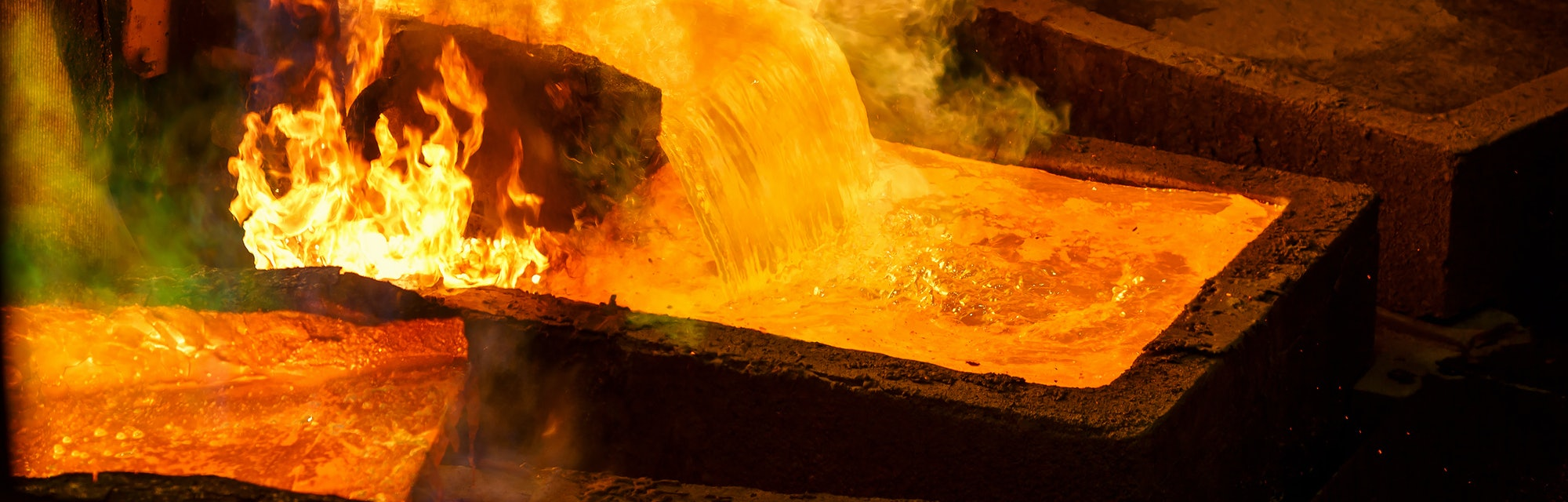Molten metal is poured into large rectangular molds for casting. When melting the evaporation of gases. Bright flames and intense heat. Copper production at the metallurgical plant. Closeup.