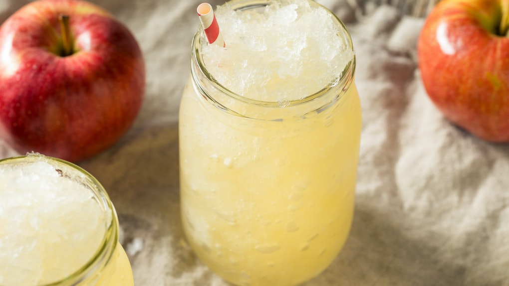 An apple cider slushie sits in a mason jar on a tablecloth with crisp apples.
