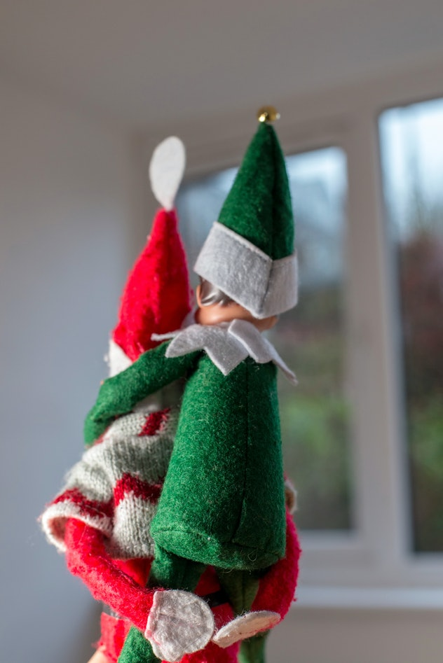 A naughty xmas elf giving another one a piggyback as they make festive mischief