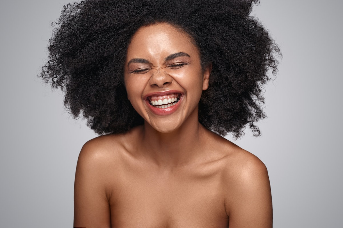 Happy young African American woman with bare shoulders laughing against gray background while repres...