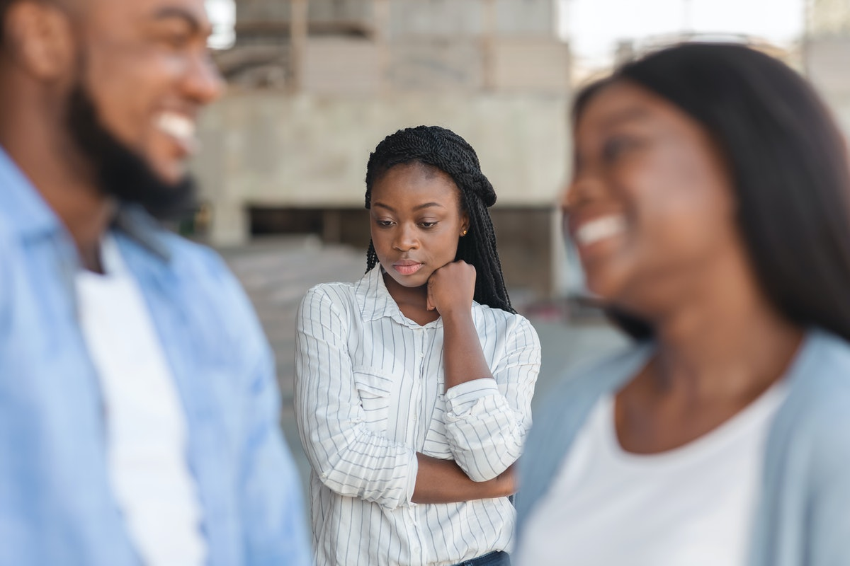 Third wheel. Upset black girl jealous to her dating friends, standing alone on background outdoors, selective focus