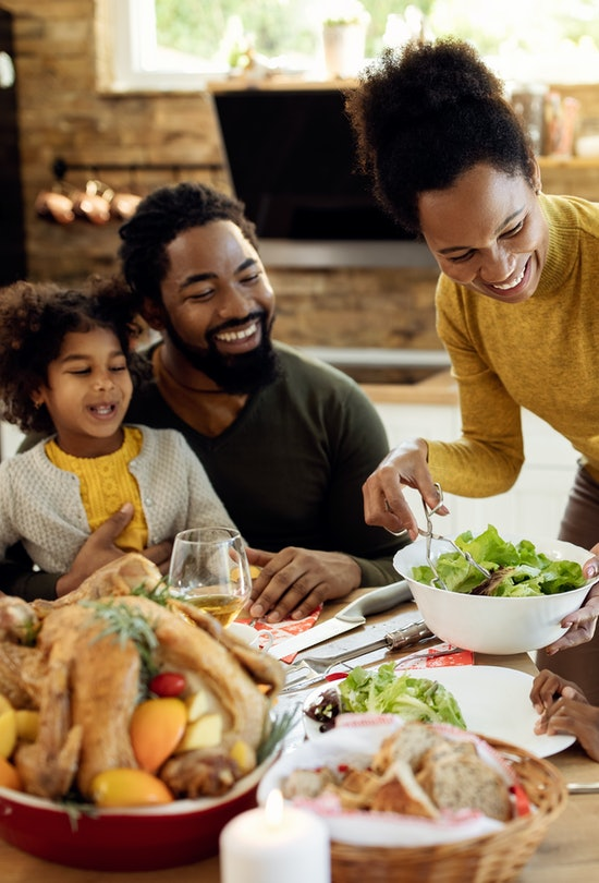 Happy African American woman having Thanksgiving lunch with her family and serving salad at dining t...