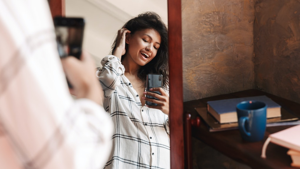 Photo of joyful brunette woman wearing shirt taking selfie photo and looking at mirror in apartment
