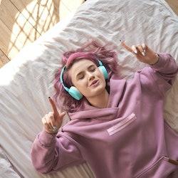 Woman listening to Alexa playlist via headphones on her bed.