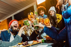 Group of friends drinking at cocktail bar with open face masks - Happy young people having fun together toasting drinks at nightclub - New normal lifestyle concept. Focus on left glass.