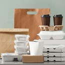 Different packages and carton cups on table against color background. Food delivery service