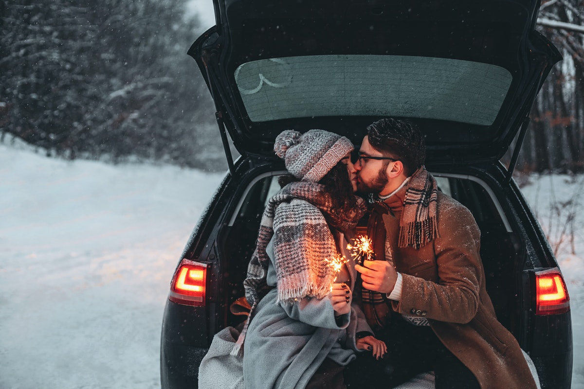 A couple sitting at the back of a car and having picnic in a snow forest. Winter romantic atmosphere. Celebrating Christmas. Happy Valentine`s day.