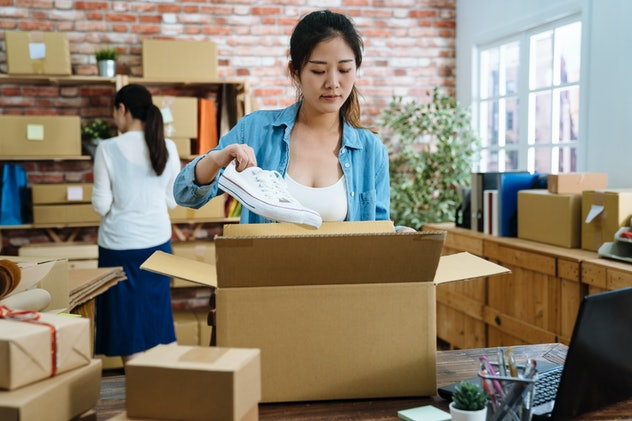 Startup small business entrepreneur SME freelance woman work with box. Young Asian lady worker in office online marketing packaging parcel delivery e commerce concept. girl packing shoes in cardboard