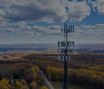 Aerial view of mobiel phone cell tower over forested rural area of West Virginia to illustrate lack ...