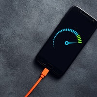 Smartphone connected to a usb charging cable and fast charging on black background. Phone fast and q...