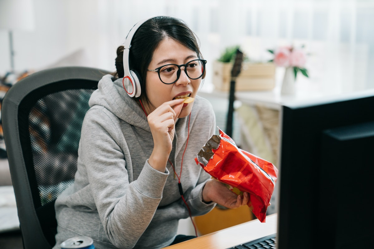 funny young asian woman otaku sit at home with pack of snacks in his hands eating chips and watching...