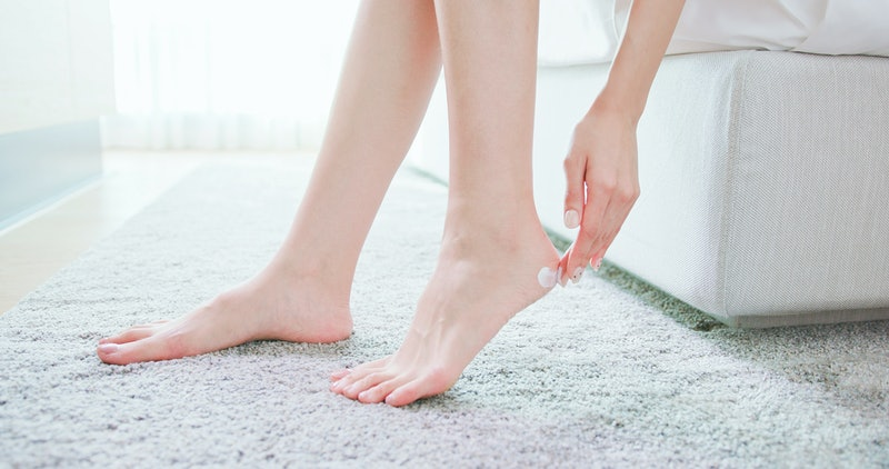 Skin care concept - beauty woman apply lotion or cream with foot at home