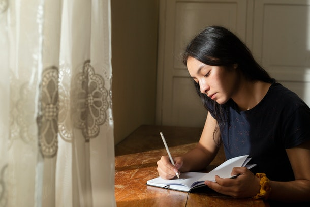 Young Hispanic woman writing in a notebook, serious girl writing in her journal in her room at sunset. concentrated young woman studying at home