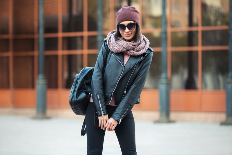 Young fashion woman with backpack walking on city street Stylish female model in leather jacket beanie scarf and black skinny jeans