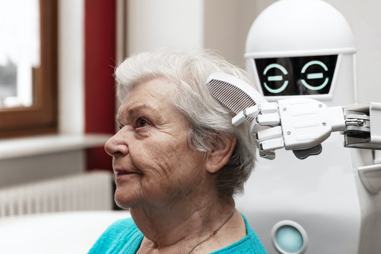 a robotic caregiver is combing the hair of a female senior adult, concepts like household nursing ro...