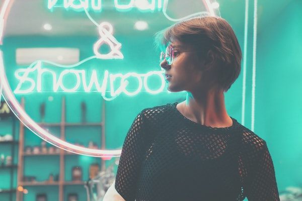 Hipster teen tomboy girl pretty face short hairstyle wear stylish glasses on neon sign background, blue pink street light fashion trendy teenager young woman profile view in glowing night city style