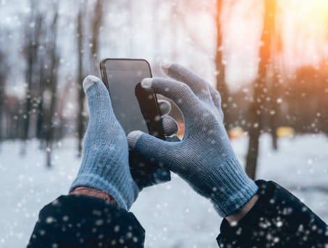 Man using smartphone in winter with gloves for touch screens. Backgound