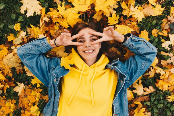 Autumn walk. Woman portrait. Happy girl in yellow hoodie and jean jacket is smiling and gesturing while lying on the ground in the park; top view