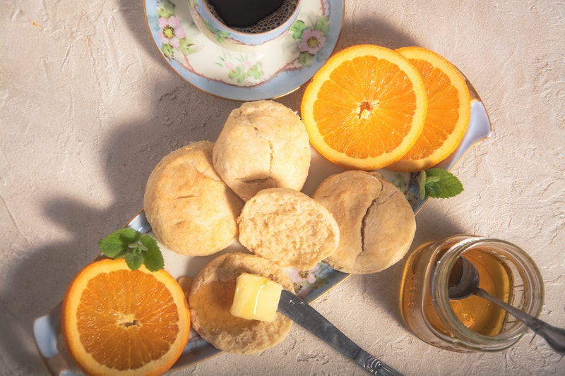 Fresh-baked biscuits with real butter and tupelo honey.  Accompanied by navel orange slices and a hot cup of coffee.