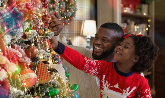 Christmas fun with daddy. Little black girl helping father to decorate family Xmas tree, enjoying wi...