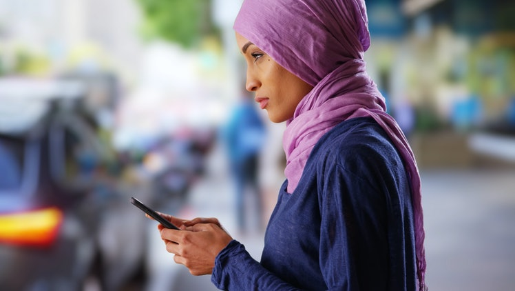 Black female in her 20s wearing hijab texting on cellphone on urban street